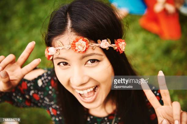 Portrait of young boho woman making peace sign at festival