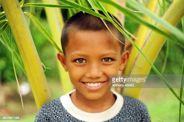 portrait of young boy amid green dense vegetation Banda Aceh Sumatra Indonesia