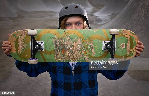 Portrait of young boy at a skate park with a skate