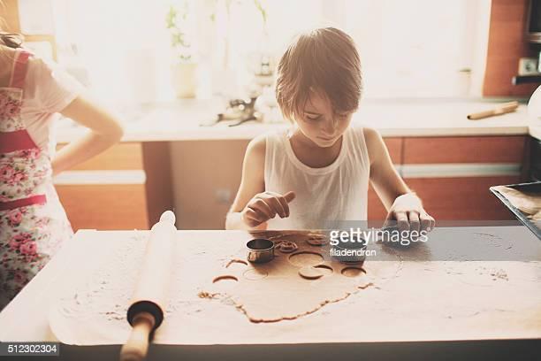 Portrait of young boy cutting dough