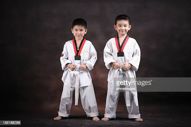 portrait of  young boy doing karate moves - taekwondo kids stock photos and pictures