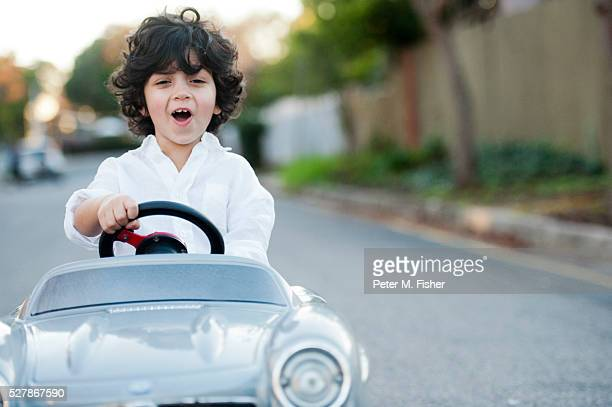 Portrait of young boy ( 2-3 ) driving toy car