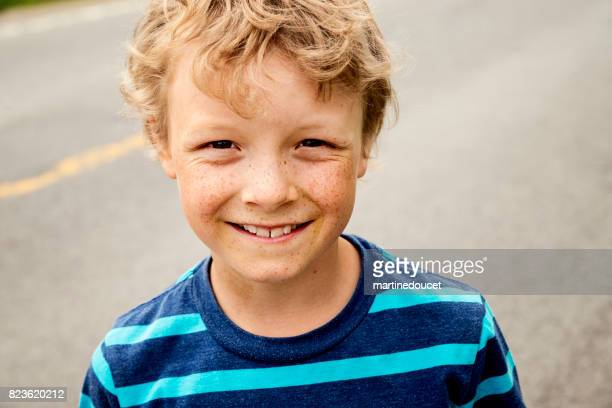 Portrait of young boy in rural street.