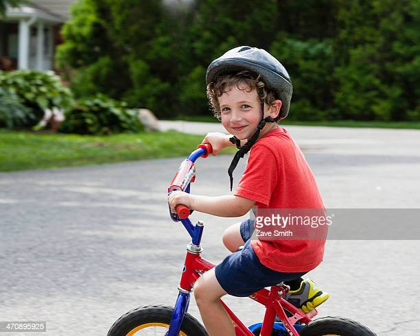 Portrait of young boy riding bicycle on driveway