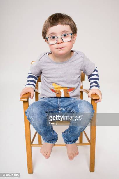 Portrait of young boy sitting in wooden chair
