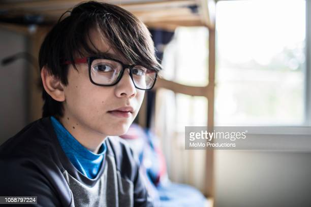 Portrait of young boy sitting on bed at home