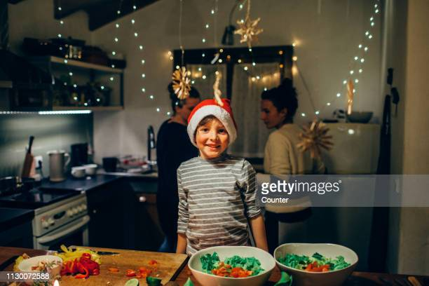 portrait of young boy smiling in kitchen preparing christmas dinner - pratos vegetarianos - fotografias e filmes do acervo