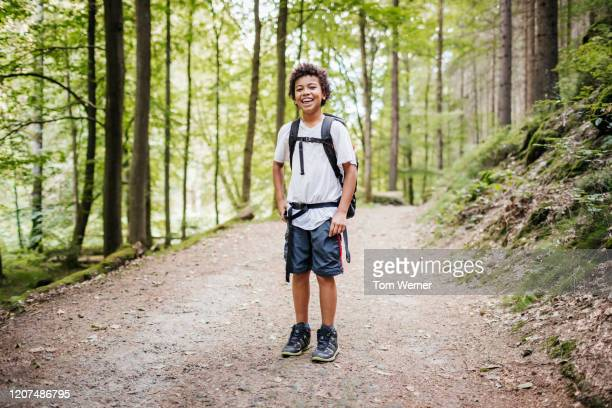 portrait of young boy smiling while hiking - alleen jongens stockfoto's en -beelden