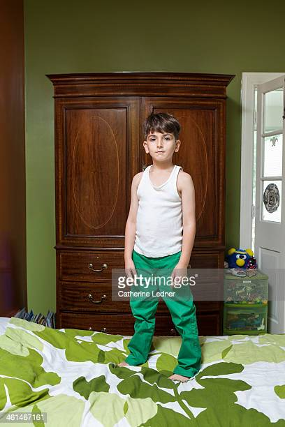 Portrait of young boy standing on a bed