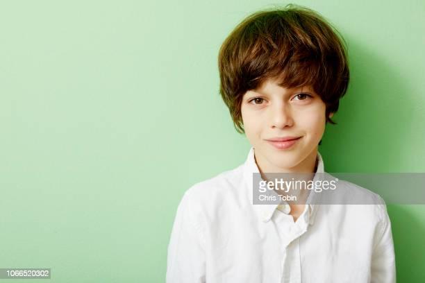 portrait of young boy with green background - alleen kinderen stockfoto's en -beelden