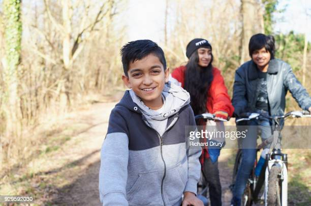 Portrait of young boy with sister and friend on cycle track