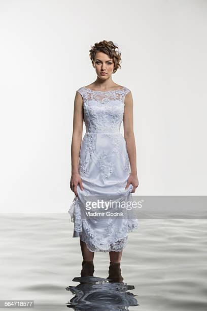 Portrait of young bride holding dress while standing in water against white background
