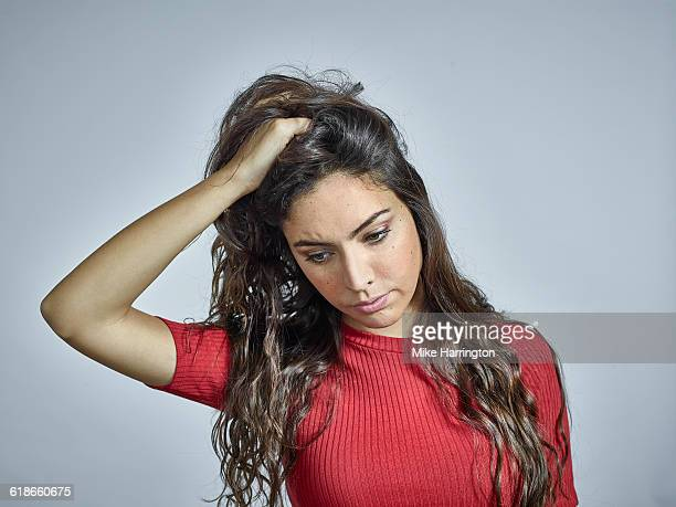 portrait of young brunette female holding hair - worried stock pictures, royalty-free photos & images