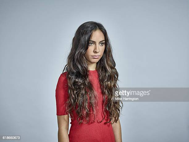 portrait of young brunette female in red dress - red dress stock pictures, royalty-free photos & images