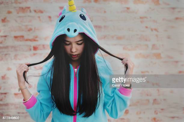 portrait of young brunette in unicorn  hooded onesie