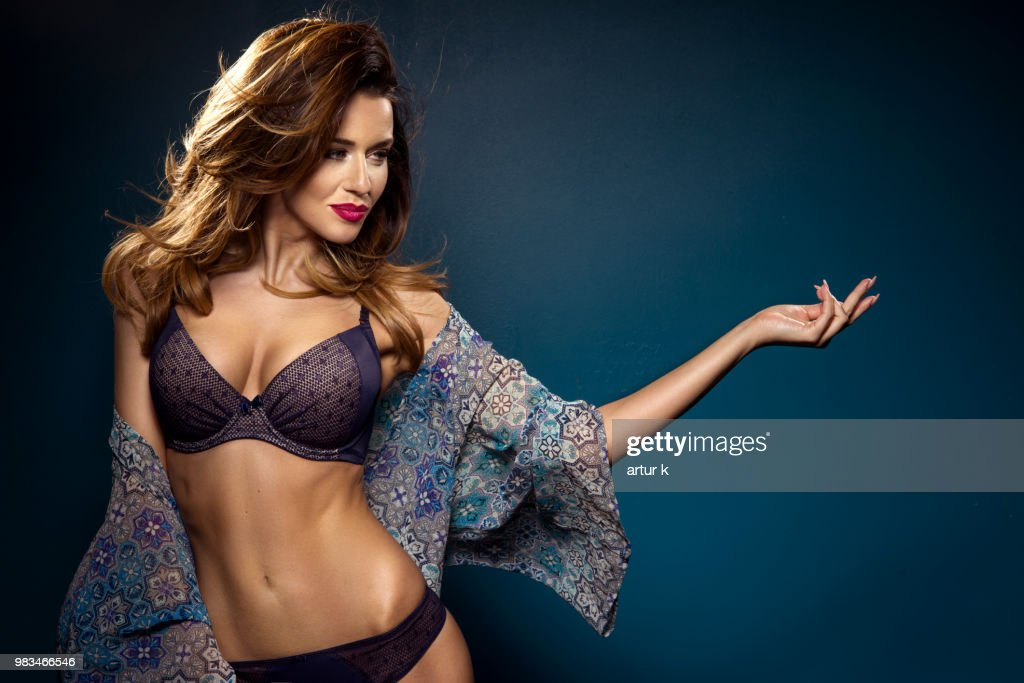 47b0b2b01 Portrait of young brunette woman in dark lingerie over blue background    Stock Photo