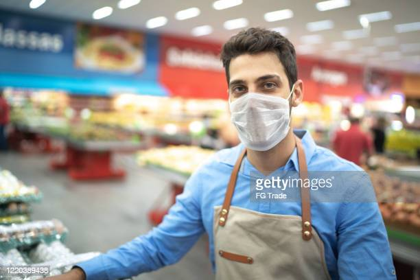 portrait of young business man owner with face mask at supermarket - groceries stock pictures, royalty-free photos & images