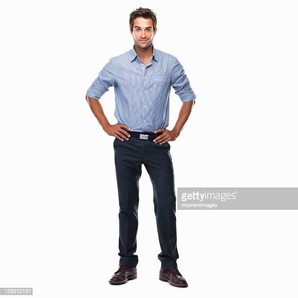 portrait of young business man standing with hands on hips and smiling against white background - handen op de heupen stockfoto's en -beelden