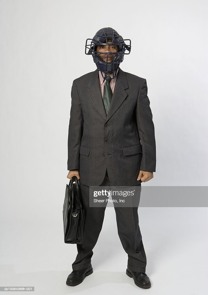 Portrait of young business man with briefcase wearing american football helmet : Stock Photo