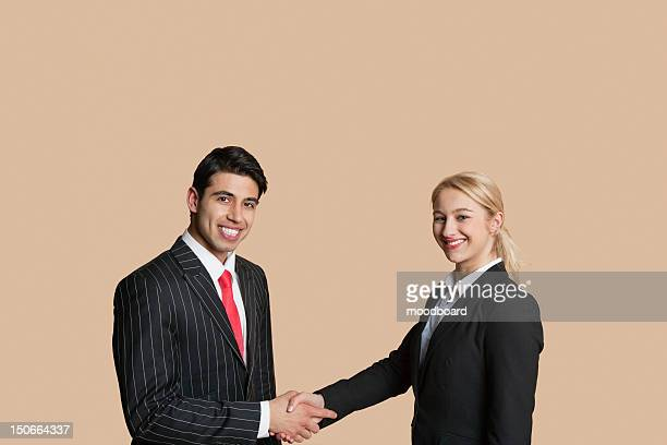 Portrait of young business people shaking hands over colored background