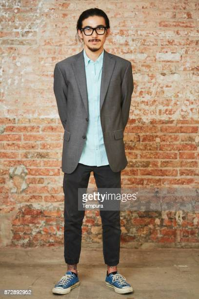 Portrait of young business person against brick wall.