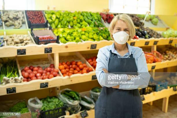 portrait of young business woman owner of grocery store with face mask - essential services stock pictures, royalty-free photos & images