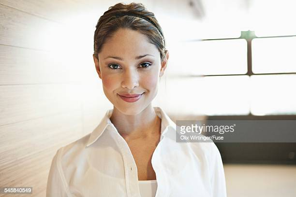 Portrait of young business woman smiling in office corridor
