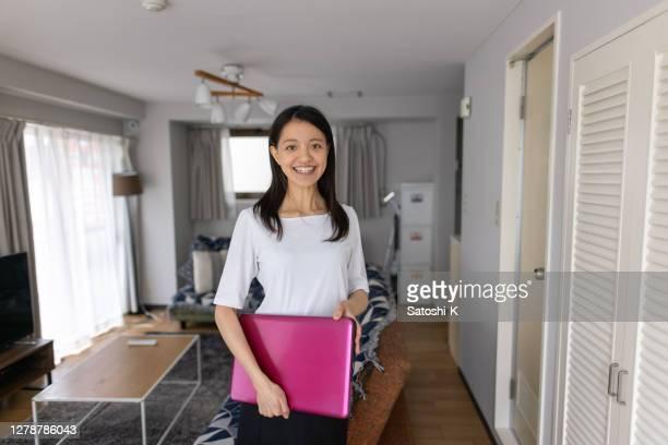 portret van jonge bedrijfsvrouw die zich in woonkamer bevindt, die laptop houdt - wit hemd stockfoto's en -beelden
