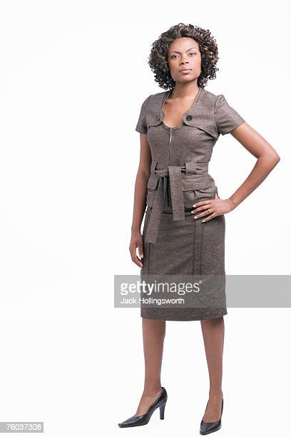 Portrait of young business woman wearing dress, standing with hand on hip