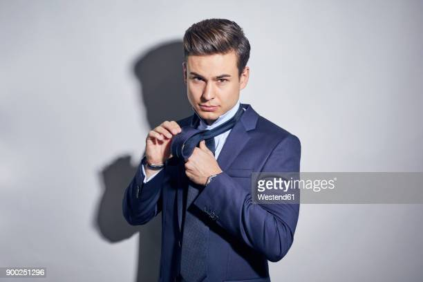 portrait of young businessman binding his tie - blue suit stock pictures, royalty-free photos & images