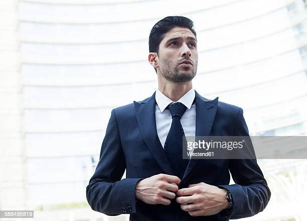 Portrait of young businessman buttoning his suit jacket
