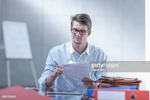 Portrait of young businessman checking documents at his desk