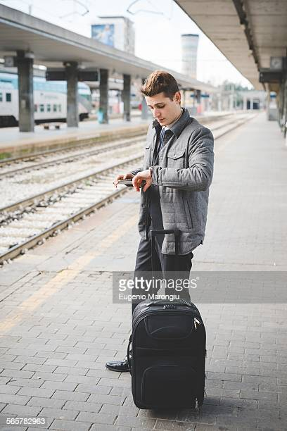 Portrait of young businessman commuter checking wristwatch for the time at train station.