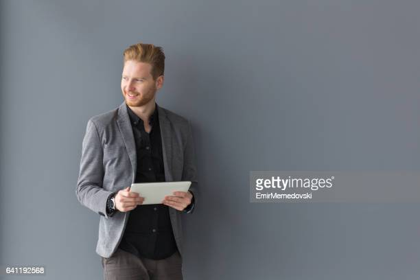 Portrait of young businessman holding digital tablet, looking content.