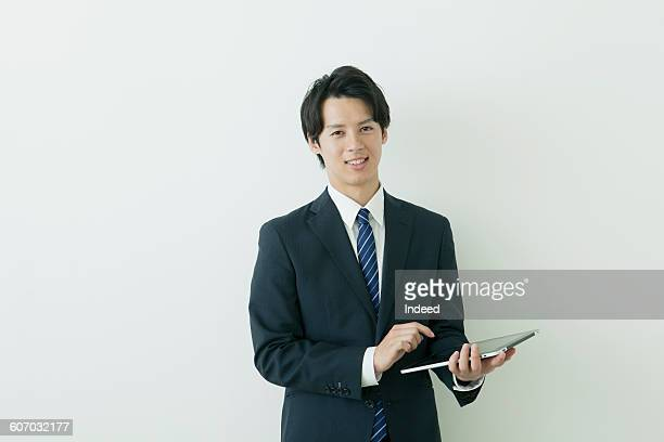 Portrait of young businessman holding digital tablet