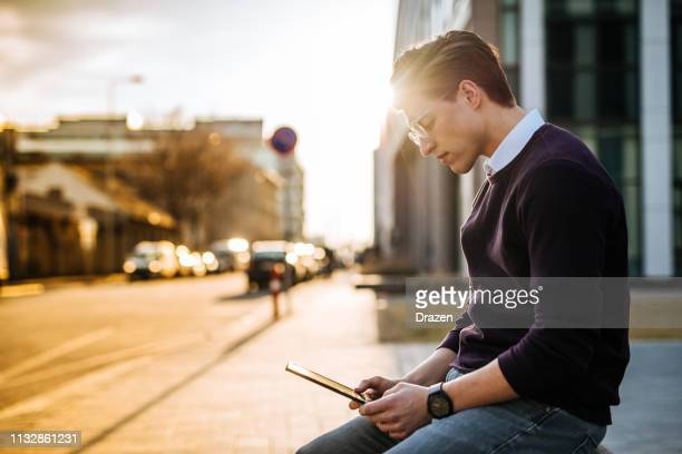 Portrait of young businessman in downtown using digital tablet on public wi-fi spot