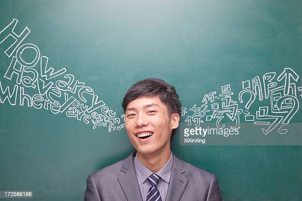 portrait of young businessman in front of black board with chinese and english script - niet westers schrift stockfoto's en -beelden