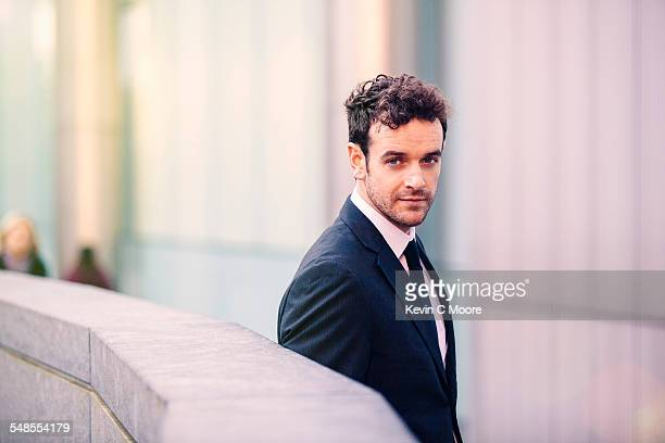 Portrait of young businessman in front of office