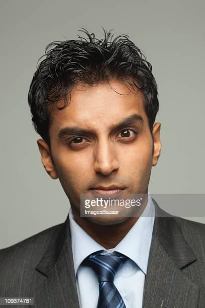 Portrait of young businessman looking uncertain, studio shot