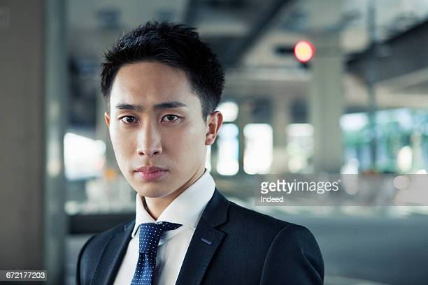 portrait of young businessman on street - 真剣 ストックフォトと画像