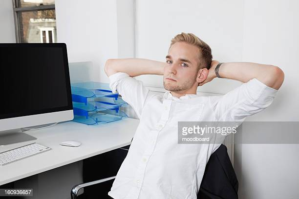 Portrait of young businessman relaxing on chair at office desk