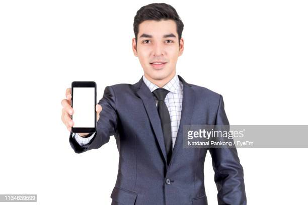 portrait of young businessman showing mobile phone against white background - mostrare foto e immagini stock