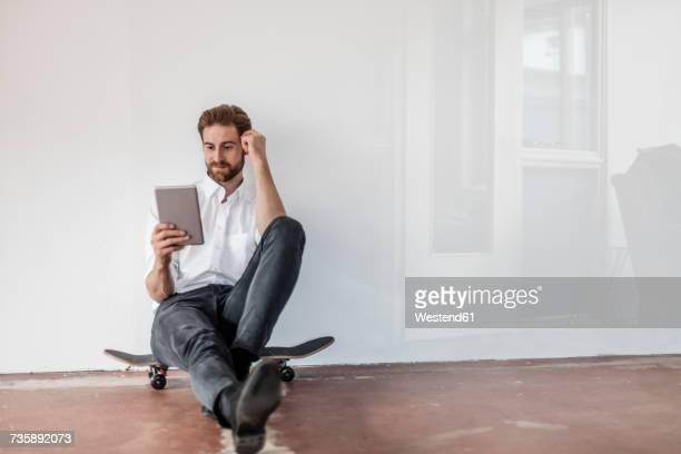 Portrait of young businessman sitting on skateboard on the floor