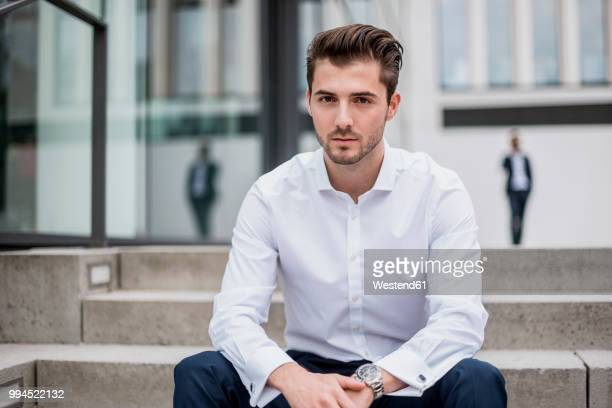 portrait of young businessman sitting on stairs - 男性一人 ストックフォトと画像