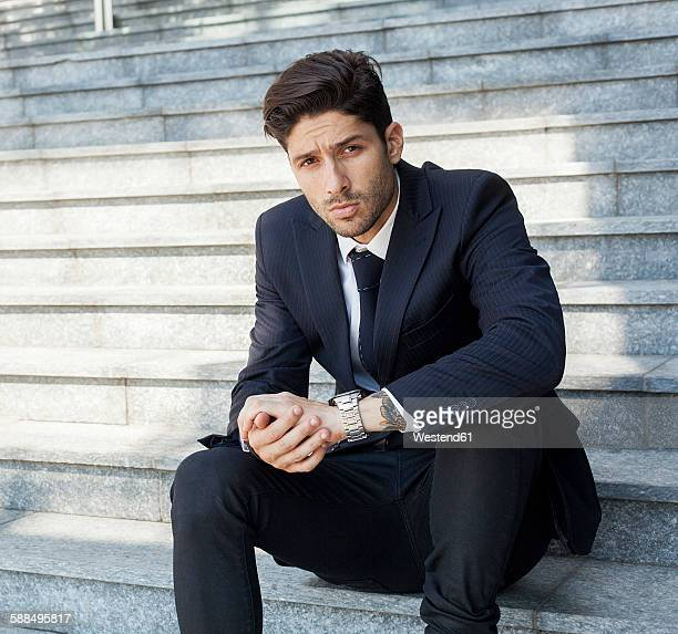 Portrait of young businessman sitting on the stairs