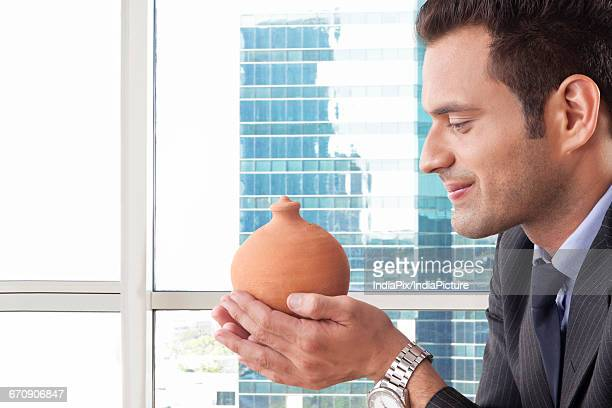 Portrait of young businessman smiling and holding a money bank
