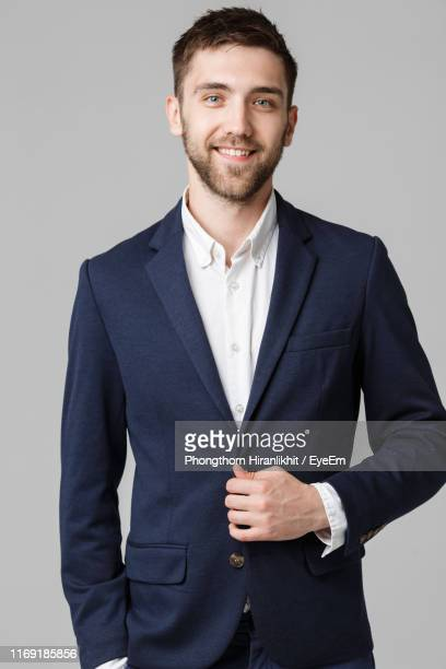 portrait of young businessman standing against gray background - blazer chaqueta fotografías e imágenes de stock