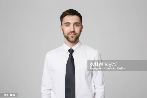 portrait of young businessman standing against gray background - das nekkleding stockfoto's en -beelden