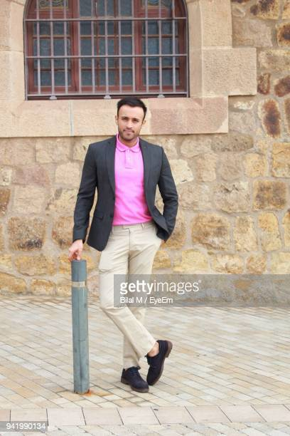 portrait of young businessman standing against wall - smart casual stock pictures, royalty-free photos & images