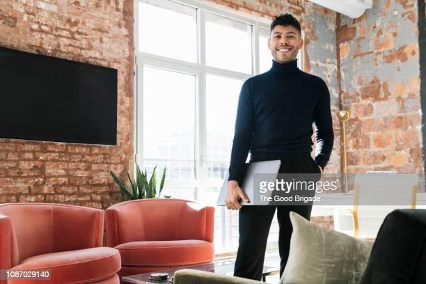 portrait of young businessman standing on office holding laptop - col roulé photos et images de collection